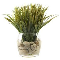 """Bring natural-chic style to your kitchen or living room with this lifelike wild grass arrangement, featuring polished river rocks and illusion water in a glass vase. Product: Faux botanical arrangementConstruction Material: Silk, glass and rocksColor: Green and naturalFeatures: Made in the USADimensions: 14"""" H x 10"""" Diameter"""