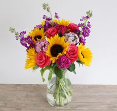 Vibrant Summer Bouquet: • 6 Sunflowers • 4 Cerise rose • 3 Purple stocks • 5 Sweet Williams