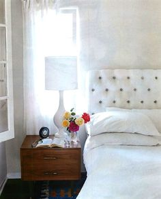 House beautiful bungalow.  White upholstered headboard.