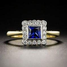 Recently crafted in Great Britain in platinum over 18K gold in, faithful emulation of classic early-twentieth century Edwardian style, this lovely low-profile charmer centers on a radiant royal blue French-cut sapphire, weighing just shy of a half-carat, framed by small sparkling white diamonds. The top measures 3/8 inch; currently ring size 7.