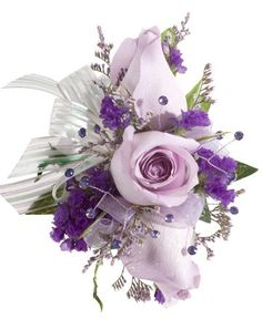 DECORATED ROSE CORSAGE, LAVENDER - A corsage with three lavender roses, purple statice, caspia, and is decorated with three purple rhinestones and a white & silver bow. Designed as a wrist corsage, but can be converted to a pin on corsage with included pins. Item #4405.