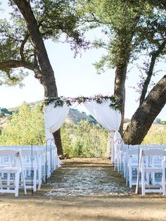 drape a white linen curtain arch outdoors for a luxurious wedding backdrop