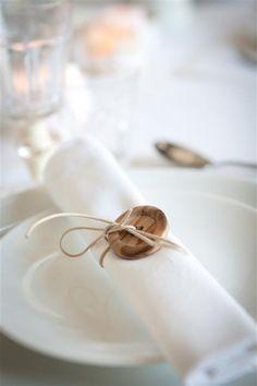 Knoop een lederen koordje rond een serviette en werk af met een houten knoop.