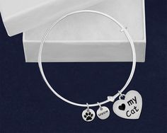 """I Love My Cat Bangle Charm Bracelet: This cute, """"I Love My Cat Retractable Charm Bracelet"""" is fun to wear and will make you the envy of all of your cat loving friends!  This beautiful bracelet has an 1 inch x 1 inch two sided silver heart charm that says """"Heart my Cat"""" on one side and has a black paw print on the other side.  It also has two additional 3/8 inch silver charms on it...  One which says """"meow"""" and the other one simply has a black paw print on it."""