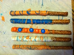 Chocolate dipped pretzels sticks!!! Chicago bear colors. M's-candy melts Wilton orange dark blue and white,,,sprinkles...  Easy snack I did these for a fundraiser in honor of Mike.