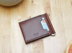 $50 Description: This bi fold leather wallet features a sleek gold tone money clip. The full-grain, vegetable-tanned leather is made from the finest