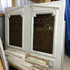 Beautiful antique iron French doors make a beautiful queen headboard, painted white.