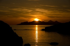 Sunset over the isles of Eigg and Rhum, west Scotland by dandraw, via Flickr.