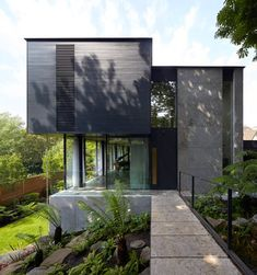 London firm Stanton Williams has completed a house in leafy north London with a timber and stone exterior, green sedum roofs and an entrance that brings residents over a bridge