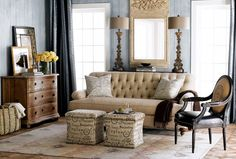 """Ornate candlestick lamps and a carved Trumeau mirror go for Baroque, while pillows and ottomans show the """"write"""" stuff. A serpentine chest adds rustic charm. from Horchow"""