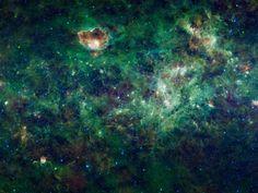 Essa foto é na verdade um mosaico de imagens construído através de pesquisas da NASA, que mostra uma seção enorme da Via Láctea. Nela, os pontos azuis são estrelas, e as áreas verde e vermelha representa a luz emitida principalmente pela poeira interestelar