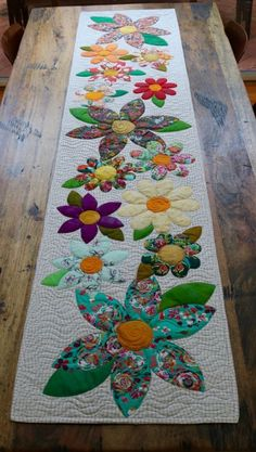 Blossoms Table Runner Paper Pattern – Free Bird Quilting Designs 2019 - - Wedding Decorations 2019 - World TrendsThe Blossoms table runner is an easy project perfect for a quick finish. The appliqué is made up of simple shapes and is laid onto the Table Runner And Placemats, Quilted Table Runners, Patchwork Table Runner, Quilted Table Runner Patterns, Quilted Table Toppers, Fall Table Runner, Fall Placemats, Table Topper Patterns, Patchwork Quilting