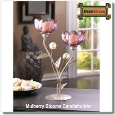 Mulberry Blooms Candleholder - Decorate your space with the shimmer of mulberry hued candlelight and pearly shine. Two flowery candle cups await the candles of your choice, and their silvery stems are decorated with pearly buds that will shimmer in the light.