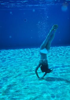 The outdoor swimming pools of the 5 Star Luxury Hotel Suites La Residence Mykonos are deep, cool and blue. Ideal for swimming. In the photo a girl is diving to the bottom of the pool.