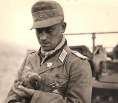 A Panzerleutnant of the Afrika Korps holds a pigeon. Unusually, he wears his Iron Cross 2nd Class ribbon on the pocket buttonhole and a single large panzer skull. He's also wearing a zip-up sweater underneath.