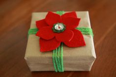 Simple present topper:  Two felt poinsettia petals secured with a button through the middle.