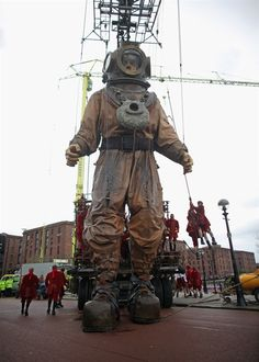 """A giant deep sea diver puppet, part of a street theatre production entitled """"Sea Odyssey,"""" walks through the streets in Liverpool, England, on April 20."""