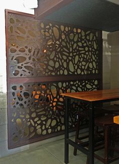 Laser cut decorative screens at The fig & Olive Cafe on Phillips Island. These are QAQ's 'Cayman; design in Jarrah-stained compressed hardwood.