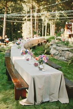 A long, picnic-style reception table decorated with colorful flower arrangements and lined with casual wooden benches.