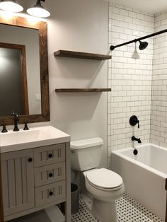 Farmhouse bathroom. Wall color - Eider White by Sherwin Williams. Subway tile and tub from Menards. Basket weave black and white floor tile found locally. Martha Stewart Vanity from Home Depot. Kohler faucets. Special walnut wood stain by Minwax #tilebathtub