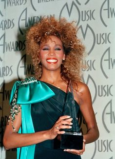 The late Whitney Houston was all smiles in a black dress with a big turquoise bow for the 1986 American Music Awards. American Music Awards, American Singers, Billboard Music Awards, Whitney Houston Pictures, I Look To You, Celebrity Deaths, Beautiful Voice, Music Icon, Christina Aguilera