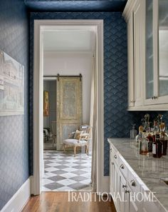 A Cole & Son wallpaper on the walls and ceiling wrap the narrow butler's pantry in dreamy blue. - Photo: Nathan Schroder / Design: Julie Dodson