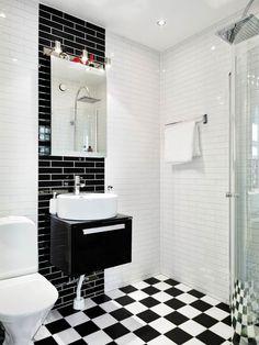 Open plan. Interesante contraste blanquinegro de azulejos que hace resaltar el lavabo y el piso en damero. LA puerta móvil delimita el espacio de la regadera cuando estáen uso.
