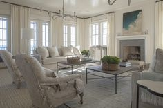 @urbangraceinteriors Double coffee tables, double sofa, double chandeliers.