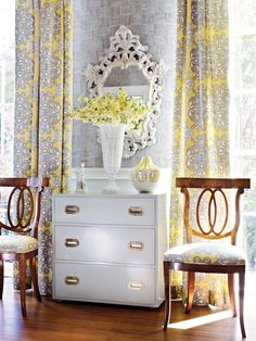 These gray and yellow toile living room curtains bring vibrance into this space and match the cushions of the chairs. The color scheme is brought together by the gray wallpaper and white dresser with yellow flowers.