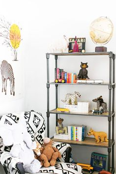 A child's bookshelf with toys, books, and a globe. #tinylittlepads @tinylittlepads www.tinylittlepads.com