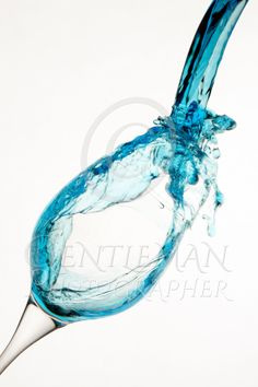 Wine glass on a white background with blue water pouring in creating a splash as the water falls away.