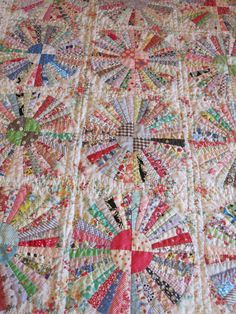 Carousel Quilt Pattern - $15.90 - Etsy - This pattern has been designed to be hand pieced.  It is the latest published pattern from Everyday Quilts and Sandra Boyle. This wonderful scrappy quilt is made up of 16 wedged circles set in a background, a pieced diamond border and the addition of some yo yo forms to add texture to the quilt. The quilt measures 72 x 72 inches square or 183.5 x 183.5 cms
