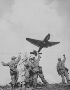Four German paratroopers salute to a  bomber Ju-87