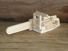 Original design wooden toy or model chainsaw. Made from pine, spruce and maple and glued together with a child safe glue. Chainsaw has no moving parts and is 13 1/2 inches long, 4 inches wide and 4 inches tall. (About 40 percent scale of a real chainsaw). The chainsaw has no oils,