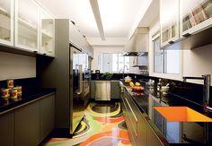 Apaixonado por gastronomia, o morador queria uma cozinha espetacular. O destaque é a cuba laranja, à dir. na foto, que faz o link com o colorido do piso grafitado e protegido com resina. O projeto é da equipe do Superlimão Studio