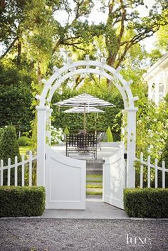 This European-inspired backyard and garden offers an elegant retreat complete with a white picket fence, blooming plants and a stone terrace. Outdoor Rooms, Outdoor Gardens, Outdoor Living, Arbor Gate, Landscape Design, Garden Design, Victorian Gardens, Modern Victorian, Garden Structures