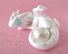 This little dragon is the first in my Gem Dragons series. She is made of high quality colored polymer clay, and finished with a gloss sealant. She is a white pearl color with pale pink accents. Her tail is curled protectively around a pearl. She is 1 inch tall, and 2 inches long. She can hold a diamond instead of a pearl upon request.