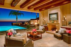 Open air porch with fireplace and view of infinity pool and ocean. Home of Yolanda and David Foster in California.