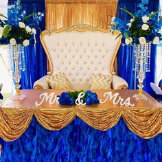 Wedding sweetheart table with royal blue curly willow skirt and gold sequin gathered tablecloth with tall floral centerpieces from CV Linens. Click to shop our collection of wedding linens, tablecloths, and drapes. Elegant sweetheart wedding decorations for blue wedding themes. Gold and blue wedding decorations for weddings on a budget. Blue Wedding Decorations, Wedding Themes, Table Decorations, Wholesale Tablecloths, 90 Round Tablecloths, Tulle Table Skirt, Sweetheart Table Decor, Curly Willow, Chair Sashes