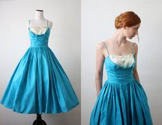 Stunning vintage early 1950's bright adraitic blue cocktail party dress with a classic, bombshell shape. Shelf bustline with an inset cream colored shelf that has decorative pearl and diamond like beads. Fully pleated skirt and a rouched top with thin spaghetti straps.