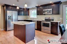L-shaped kitchen with island; dark wood cabinets, add quartz counters and white subway tile backsplash