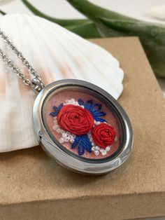 This silver oval glass locket pendant necklace features red silk ribbon roses with blue leaves and white buds on 100% pure pink wool felt.