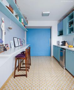Cozinha com marcenaria em tons de azul e piso de ladrilho hidráulico amarelo.