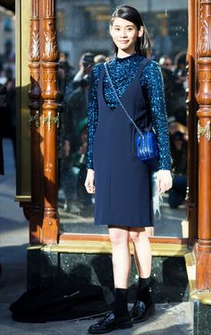 A sequined blue top is layered under a pinafore dress, worn with a crossbody bag and oxfords