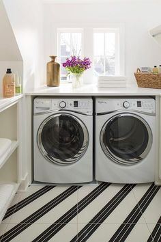 Bright, white laundry room features an enclosed washer and dryer placed under window atop a diagonal white and black porcelain tiled floor.