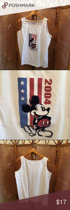 Patriotic Mickey Mouse tank top GUC Disney Store 100% cotton white tank top from 2004. Classically posed Mickey Mouse on front. Vertical stylized red, white, and blue American flag behind Mickey along with the year 2004. Back is solid white. All items come from a smoke free home. Measurements available upon request. All questions are welcome. Disney Shirts Tank Tops