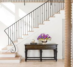 Master the Blend. If you like understated interiors that soothe rather than excite, you'll love staircases that tread lightly into view. Keep the serene scene noteworthy by designing a staircase that plays off the colors of surrounding flooring and furniture but that takes it up a notch with duo-tone stair treads and an iron railing featuring a kicky newel treatment and supporting brackets.