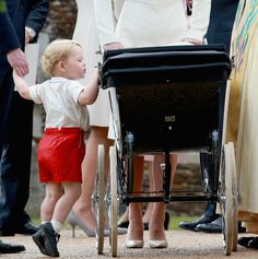 Prince George looks in the pram with his sister Princess Charlotte in