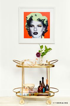 Gold bar cart and hanging Kate Moss x Banksy artwork