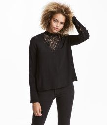Blouse in woven, crêped fabric with lace at top, small lace collar, and opening at back of neck with button. Long sleeves with flared cuffs with buttons.